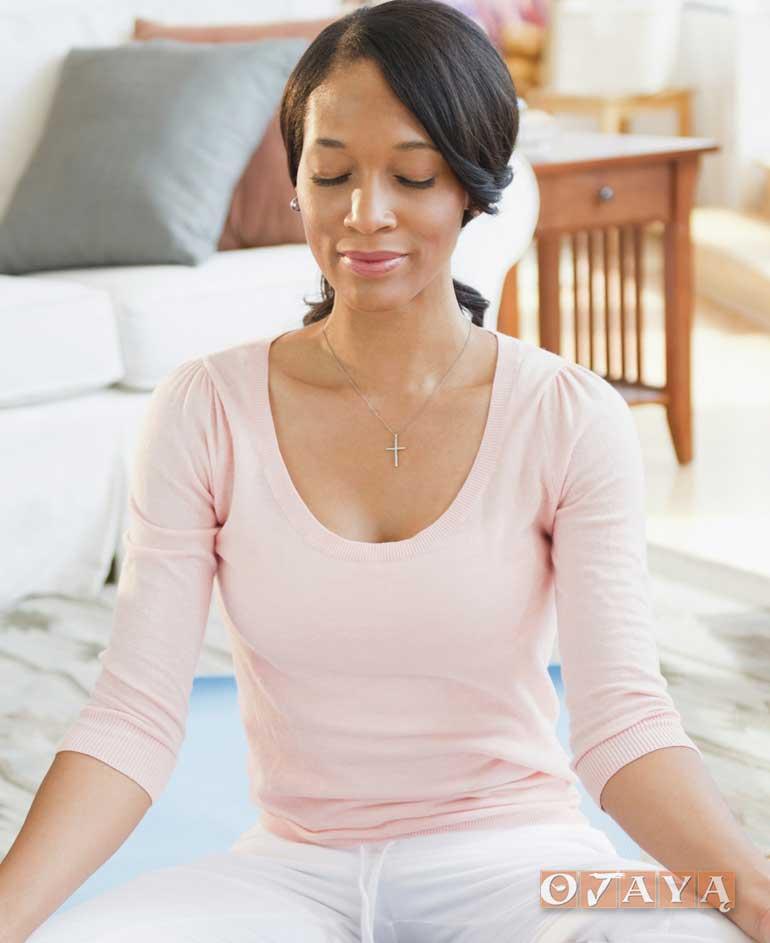 Girl meditates with headache: Efforts Create a Strain in Mindfulness