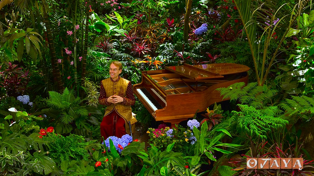 Sukaishi David teaches meditation mantras with piano in the Earthborn Rainforest.