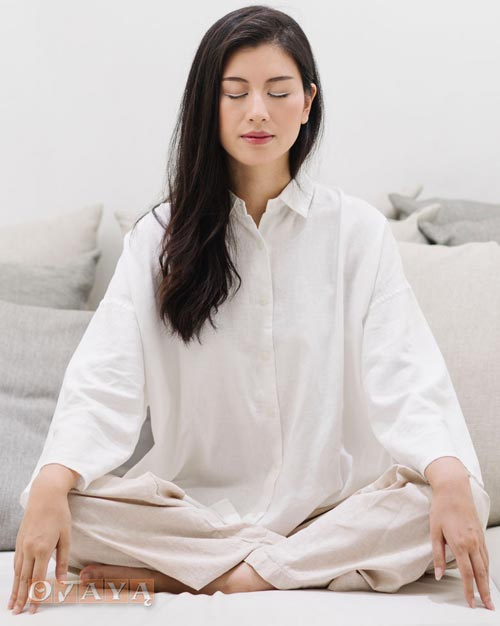 Blissful woman meditates with the OJAYA mantra to calm anxiety.